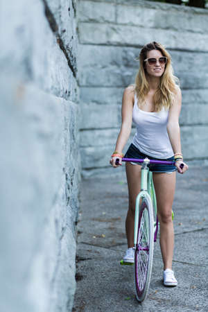 Cropped shot of a beautiful woman sitting on her bicycle Stock Photo