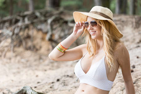 Cropped shot of a young woman wearing sunglasses and a hat sitting on the beach Stock Photo