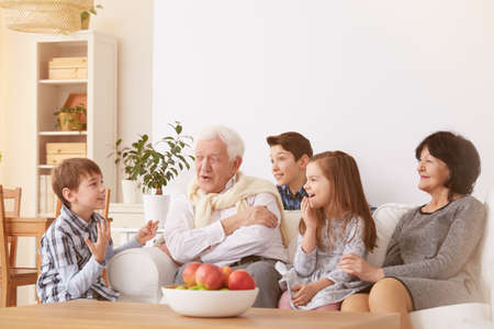 Happy children spending time with grandparents in living room