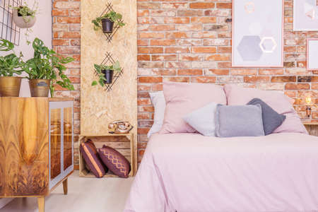 Wooden decorations and red brick wall in cozy bedroom Stock Photo