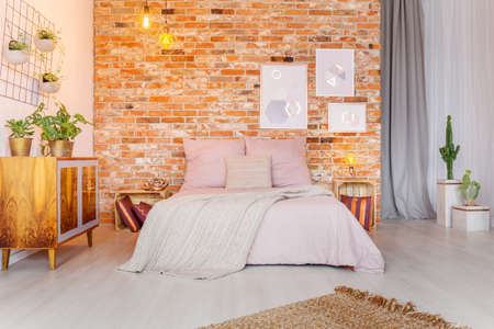 Big pink bed in cozy stylish bedroom with red brick wall