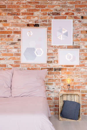 Pictures on the red brick wall in cozy bedroom