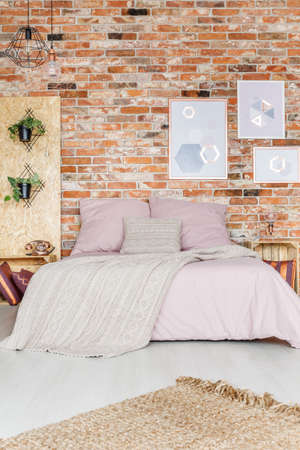 Cozy bedroom with red brick wall and pink additions Stock Photo