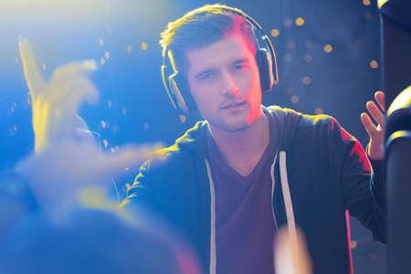 Charismatic dj weraring headphones, giving concert and nightclub