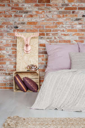 Up-to-date wooden decoration in bedroom with red brick wall