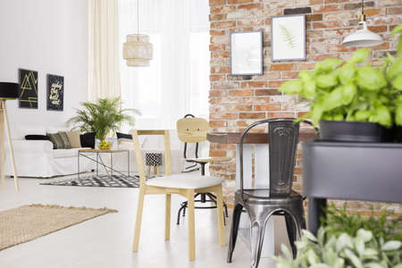 Designer chairs and red brick wall in modern dining room Stock Photo