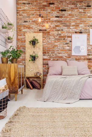 Modern cozy design of bedroom with red brick wall and wicker carpet