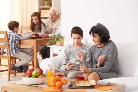 男の子のおばあちゃんにチェスをして孫を持つおじいちゃんとタブレットを使用する方法を教えて 写真素材 - 76957077