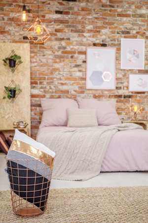 Stylish pillow in gold bin in cozy modern bedroom