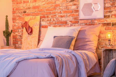 Cozy big bed by the red brick wall in stylish bedroom Stock Photo