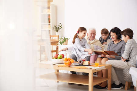 Happy grandparents showing photo album to their grandchildren in a living room Фото со стока