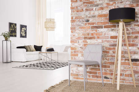 Grey designer chair and black lamp by the red brick wall