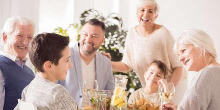 Glückliche lächelnde Familie, die zusammen während der Ferien spricht und Mahlzeit isst Standard-Bild - 76957112