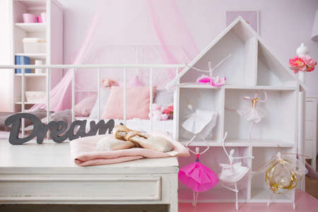 Room interior with cozy bed and stylish dollhouse