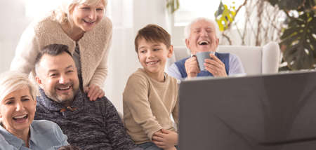 Cheerful family watching TV together during sunday afternoon Stock Photo