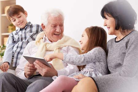幸せ孫と祖父母のリビング ルームでタブレットを使用して