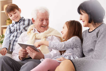 Happy grandchildren and grandparents using a tablet in living room