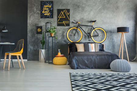 Functional bedroom interior with working area and bicycle Stok Fotoğraf