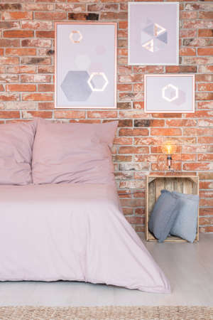 Pink comfortable bed in stylish bedroom with red brick wall Stock Photo