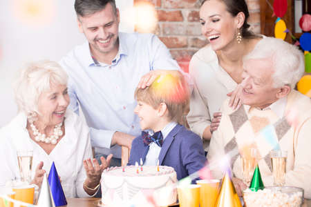 Happy family sitting together beside birthday cake Stock Photo