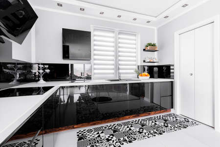 White shining kitchen with black units and decoration
