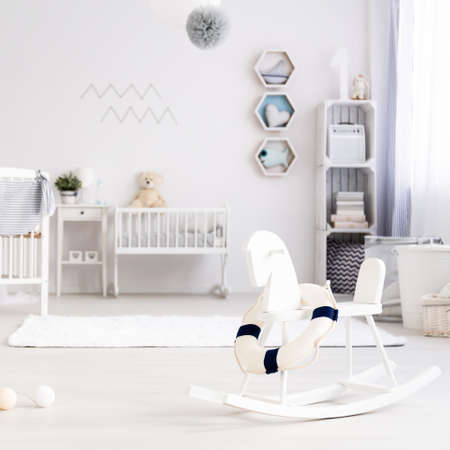 Beautiful, light baby room with white crib and rocking horse