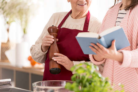 Happy grandmother holding a pepper mill and granddaughter reading a recipe book Stock Photo