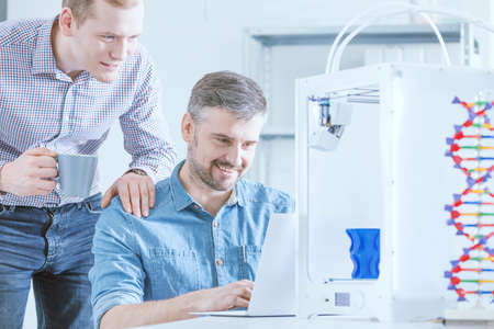 Fascinated men watching 3D print with high interest