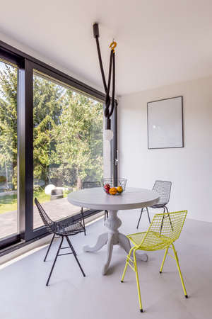 round chairs: Round table and metal chairs in small stylish dining room with panoramic window Stock Photo