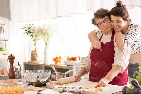 Jonge gelukkige vrouw die haar oma koestert die in een keuken kookt