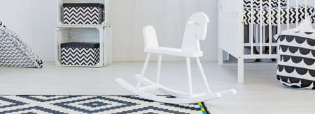 White wooden rocking horse in the middle of white and black room Stock Photo