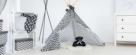 black teddy bear in the tipi tent in black and white babys room Stock Photo