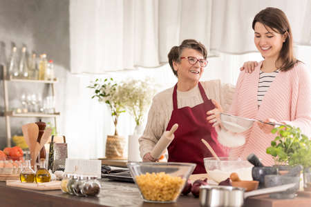Happy grandma and granddaughter baking a cake in modern kitchen Фото со стока