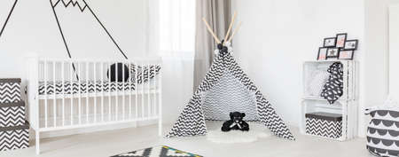 White cradle and black and white tipi tent in spacious stylish baby room