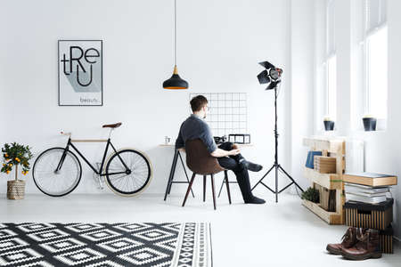 White apartment with desk, chair, bike, pattern carpet