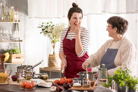 Happy granddaughter looking at her grandma while cooking Standard-Bild
