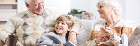 Little boy sitting on a sofa in a living room with his grandparents and reading a book