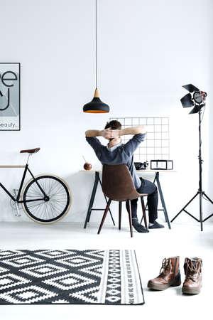 Modern, white studio flat with lamp, desk, chair, and bike Stock Photo