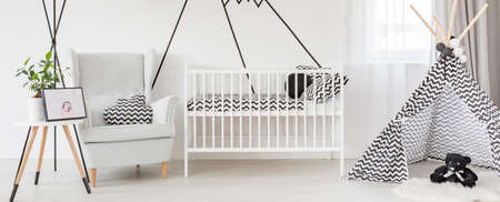 Stylish designed scandinavian style baby room with cradle and tipi tent
