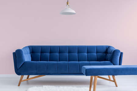 Blue sofa and bench in pink modest apartment