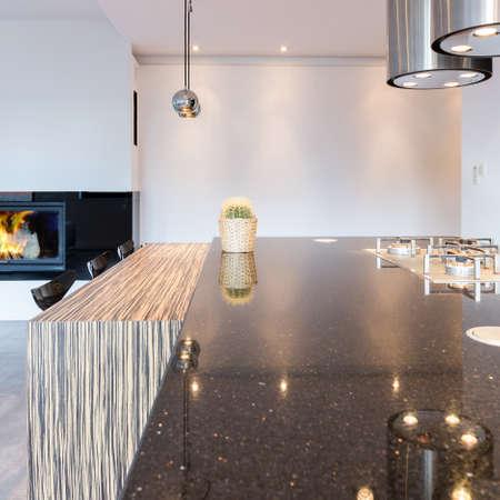 シンプルなキッチンには大きなカウンター、モダンな照明、食事バー