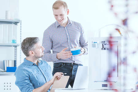 Two talking scientists in a laboratory with 3D printer