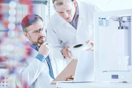 Scientists conferring in laboratory interior with 3D printer