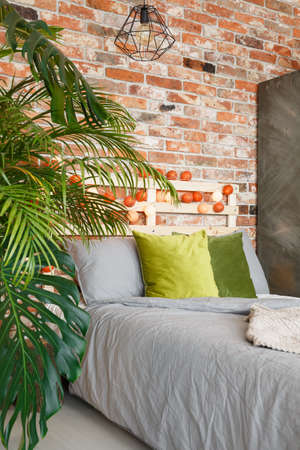 Bed and plants in modern room with brick wall