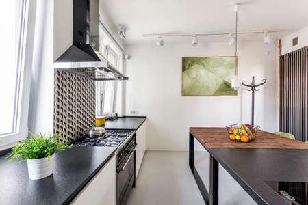 decoracion mesas: Black countertop in scandi minimalist kitchen interior arrangement Foto de archivo