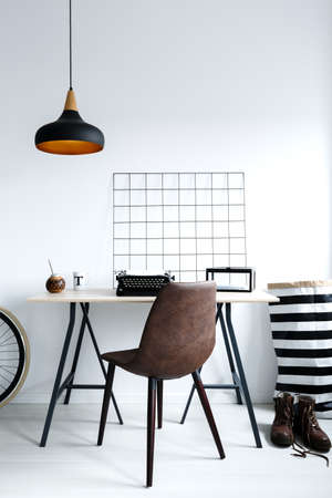 Simple, white home office with lamp, desk, chair
