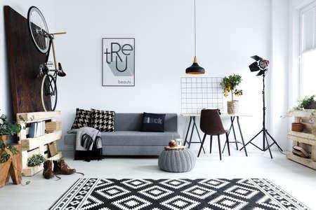 Hipster-stijl, witte woonkamer met sofa, poef, tapijt, fiets Stockfoto