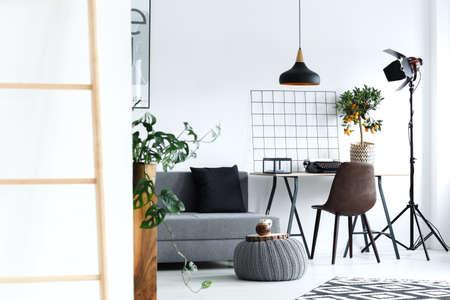 白でミニマリストな居間にグレーのソファ、ランプ、机、はしご