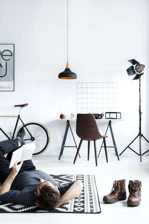 Man lying on carpet in white, simple style room Reklamní fotografie