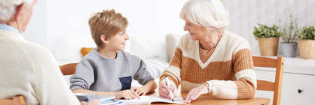 Loving grandparents helping their grandson with homework